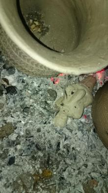figurine in bed of ashes